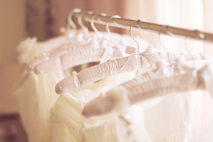 Beautiful white cream wedding dresses made of silk chiffon, tulle and lace hanging on hangers with bows